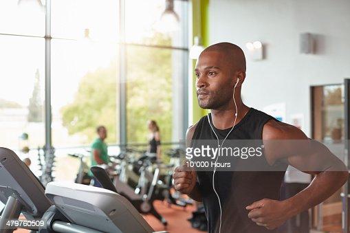 Man in a gym running on a treadmill.