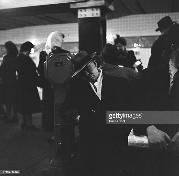 A man in a hat and coat sleeps on a bench on the 34th street subway station platform New York New York 1948 Other commuters are visible around him