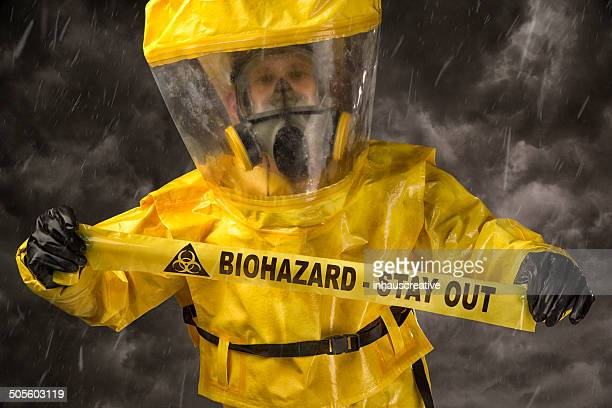 Man in a hazmat Suit holding biohazard warning tape