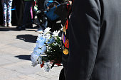 A man is a veteran of the war in a jacket with orders and medals on his chest holding a bouquet of white flowers