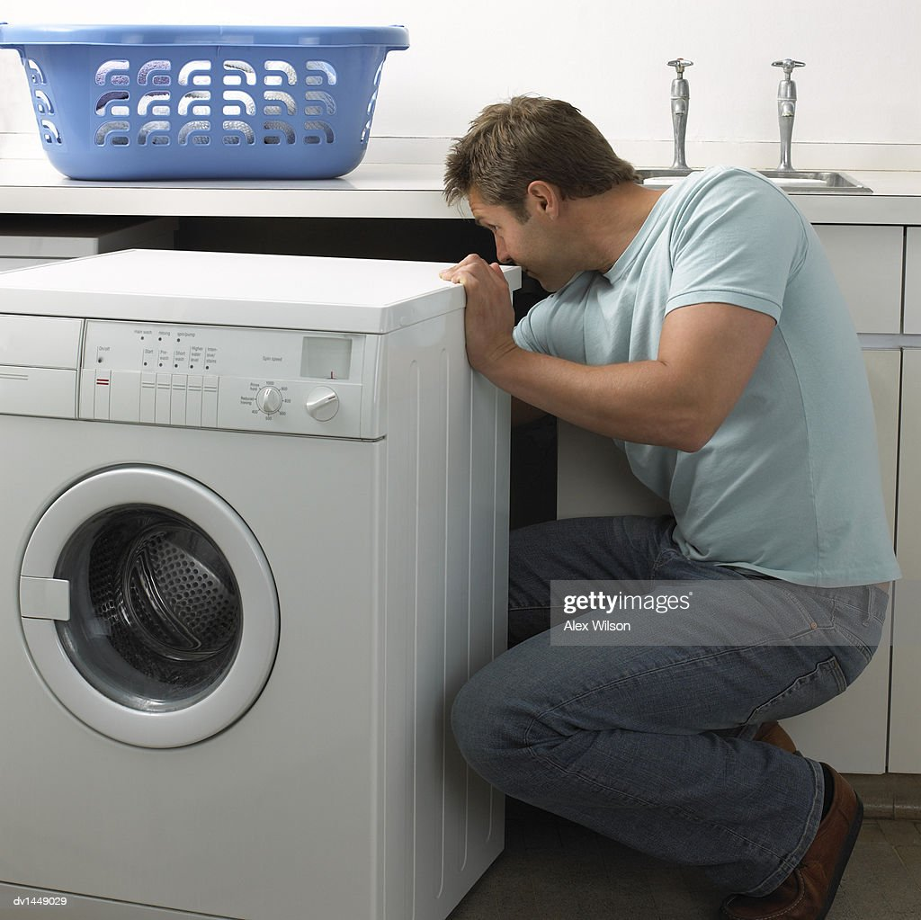Man in a Kitchen Repairing a Washing Machine : Stock Photo