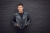 man in a leather jacket leaning on a brick wall