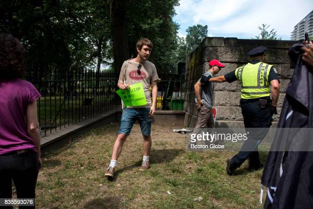 A man in a 'Make America Great Again' hat is led away by a police officer because a crowd of counterprotesters heckled him after the Boston Free...