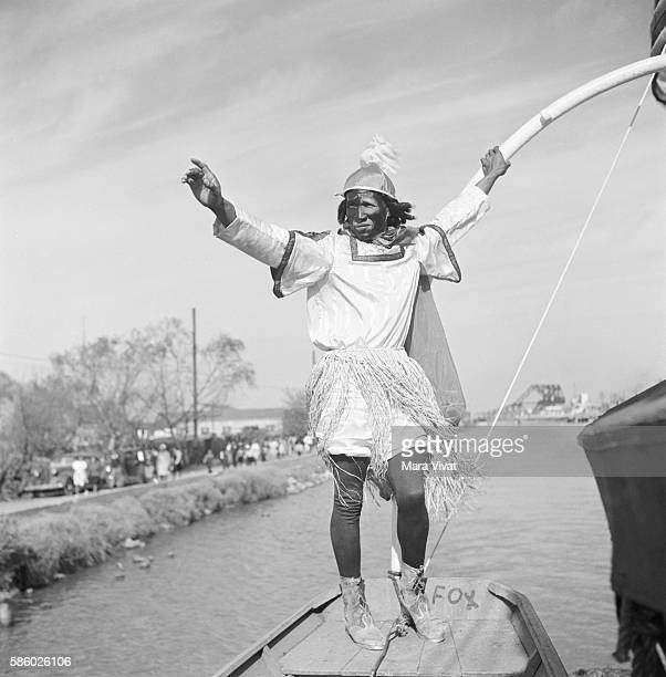 A man in a Mardi Gras boat parade on a canal wearing a costume and carrying a longbow dances New Orleans Louisiana