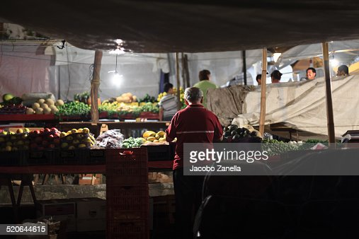 A man in a market stall at night