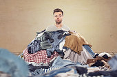 A man is covered by a heap of clothes. Funny and confused expression on his face.