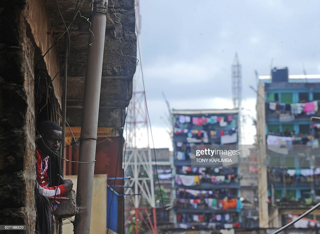 A man in a neighbouring building watches from his balcony as rescuers search for bodies trapped in rubble on May 2, 2016 at the scene of a collapsed residential building in the low-income suburb of Huruma in Nairobi. The death toll in the collapse of a six-storey building in Nairobi on April 29 rose to 21 on May 2 after four more bodies were pulled from the rubble of the residential structure that gave way during weekend storms. / AFP / TONY