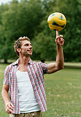 Man in a Park Spinning a Yellow Football on his Finger