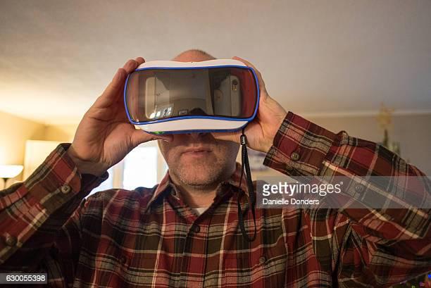 Man in a plaid shirt using a virtual reality (VR) viewer