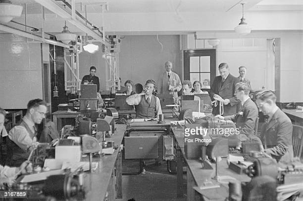 A man in a Press Association and Reuters office having a cigarette while his colleagues work on telegraph machines