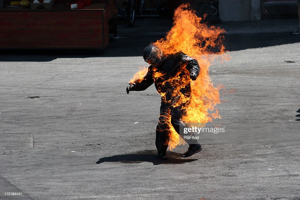 Man in a protective suit wrapped in flames : Stock Photo