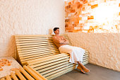 Young man relaxing in a salt room in the spa