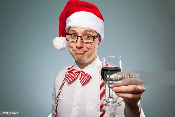 A man in a Santa hat with a wine glass and nerd glasses.