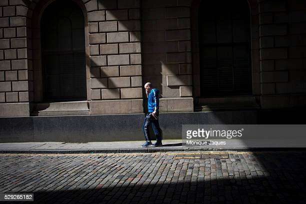A man in a Scottish sweater walks down a street in downtown Edinburgh on June 16th 2014 Views and snapshots from Scotland a country that will be...