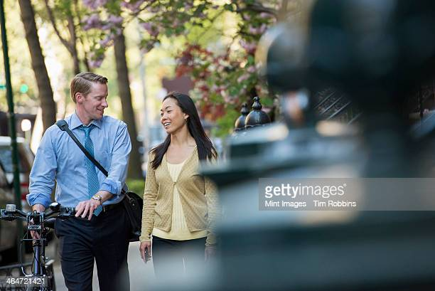 A man in a shirt and tie pushing a bicycle, and talking to a woman. A park in the city.