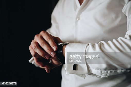 Man in a shirt looking at his watch : Foto de stock