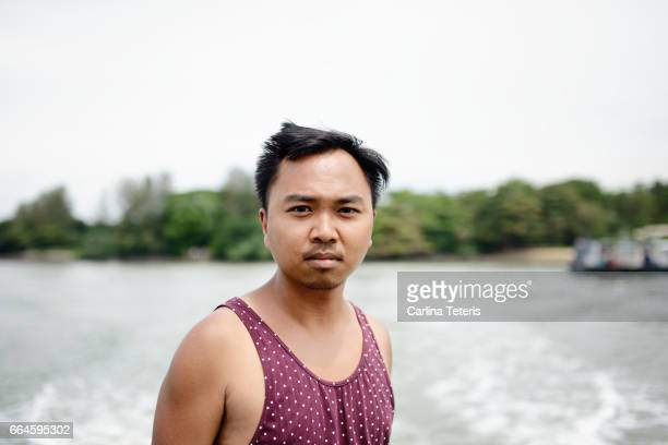 Man in a singlet on the back of a boat at Pulau Ubin