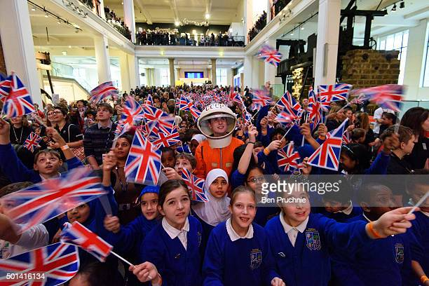A man in a space suit watches a television with school children at the Science Museum ahead of the launch of space mission Principia from Baikonur...