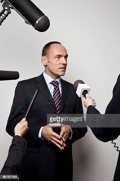 A man in a suit being interviewed by the media
