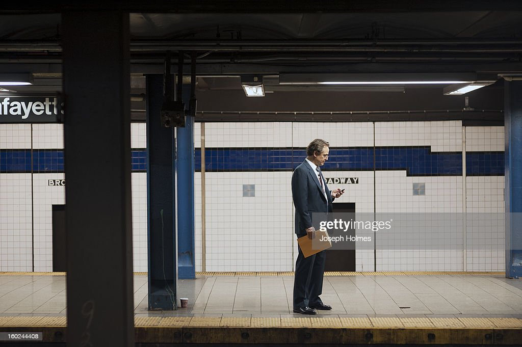 CONTENT] A man in a suit checks his cell phone while waiting for a train on the Broadway-Lafayette platform of the New York City subway.