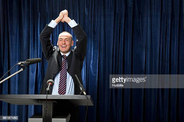 A man in a suit cheering at a lectern