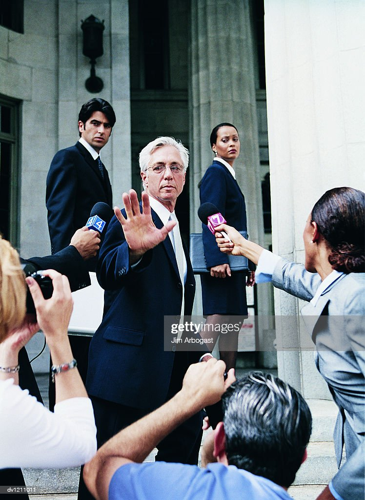 Man in a Suit Escaping From Cameramen and TV Reporters by a Building : Stock Photo