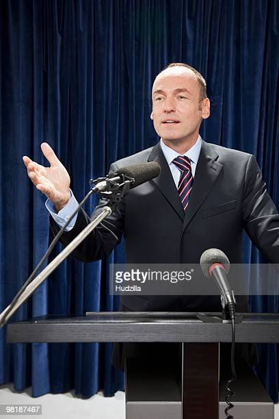 A man in a suit gesturing at a lectern