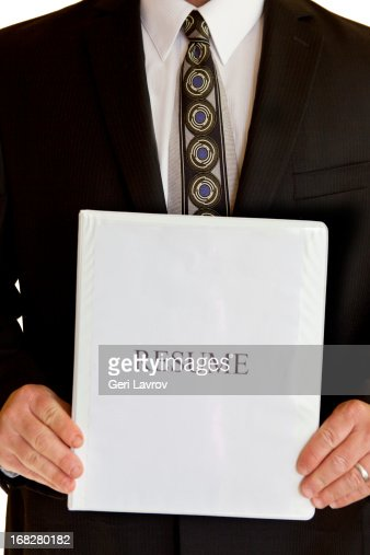 man in a suit holding a resume binder stock photo