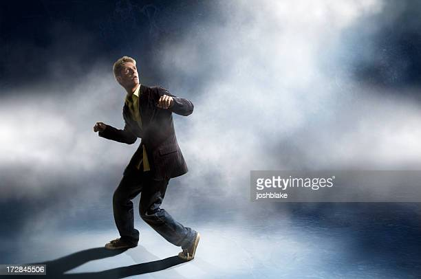 Man in a suit looking up in a ready-to-run stance