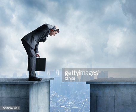 Man in a suit stares at space between two buildings