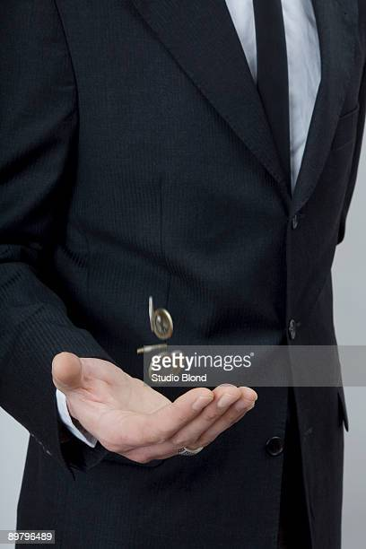 A man in a suit tossing change with his hand
