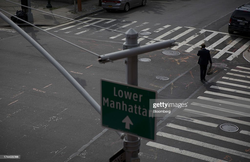 A man in a suit walks across the street under a sign directing traffic to lower Manhattan in New York, U.S., on Wednesday, July 24, 2013. The U.S. Conference Board is scheduled to release consumer confidence figures on July 30. Photographer: Scott Eells/Bloomberg via Getty Images