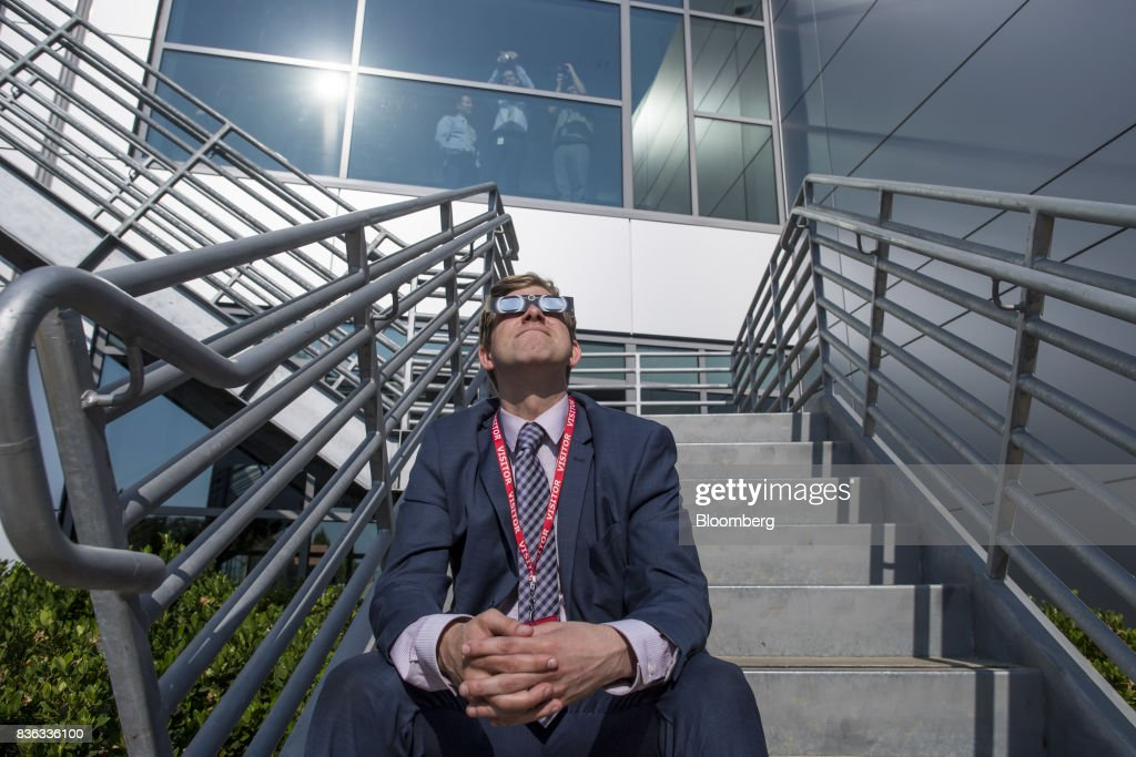 A man in a suit wears solar viewing glasses while looking at the sun during a solar eclipse at the California Independent System Operator (ISO) headquarters in Folsom, California, U.S., on Monday, Aug. 21, 2017. Millions of Americans across a 70-mile-wide (113-kilometer) corridor from Oregon to South Carolina will see the sky darken as the sun disappears from view total during the eclipse. Photographer: David Paul Morris/Bloomberg via Getty Images