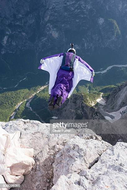 Man in a suit with wings jumping from a cliff