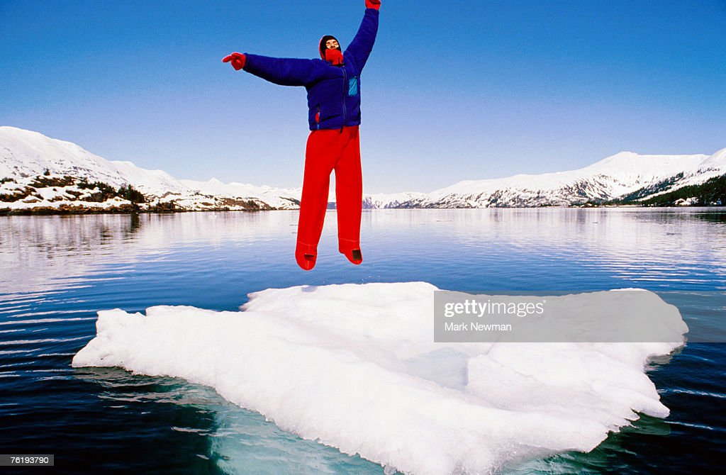 Man in a survival suit jumping on an ice floe, Blackstone Bay, Prince William Sound, Alaska, United States of America, North America : Stock Photo