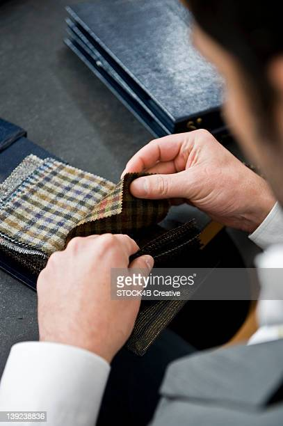Man in a tailor studio looking at fabric swatches