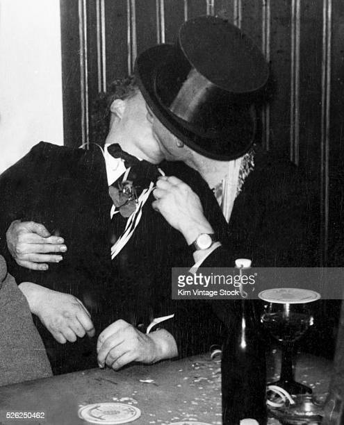 A man in a top hat embraces and kisses a woman while sitting and drinking beer