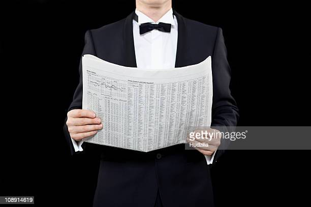 A man in a tuxedo holding a finance newspaper, midsection