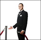 man in a tuxedo next to a velvet rope