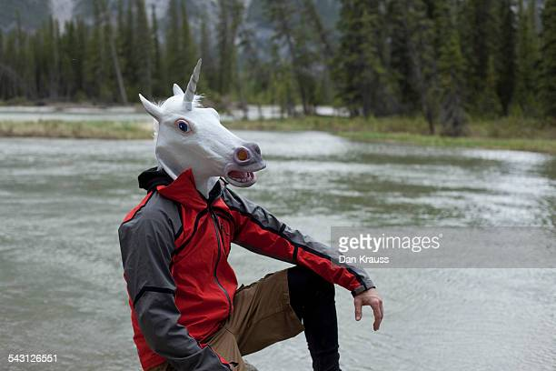 A man in a unicorn mask in the woods.