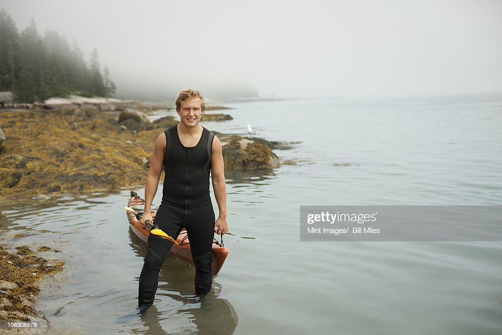 A man in a wetsuit drawing his kayak onto the shore, in misty weather. New York State, USA : Stock Photo