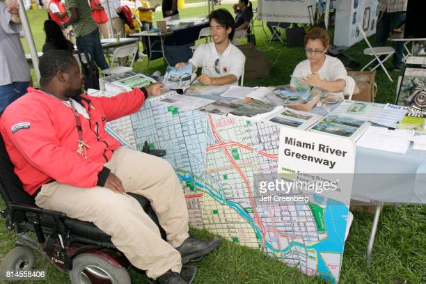 A man in a wheelchair at the Miami River Greenway booth at a fair in Jose Marti Park