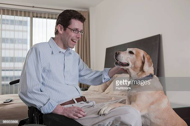 Man in a wheelchair playing with a service dog in the bedroom