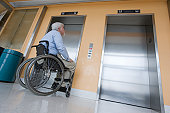 Man in a wheelchair waiting for an elevator