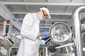 Technologist in a cap, mask and white coat is in the production shop and holding a digital tablet. inspector removes the indicators at the dairy plant. Engineer keeps statistics on production