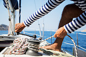 Young handsome sailor pulling rope on sailboat