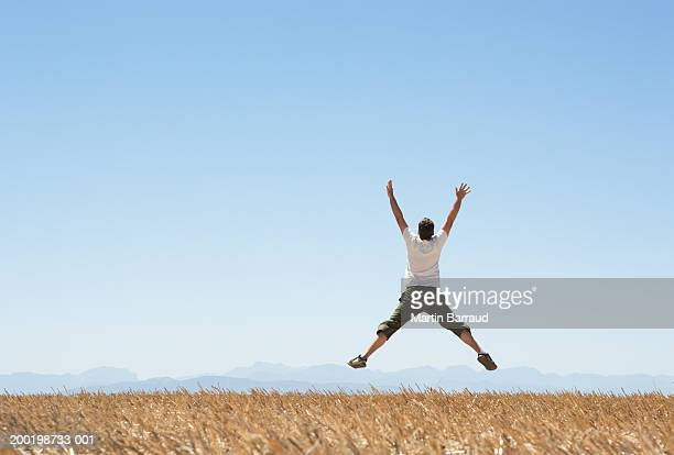 Man in air, arms and legs outstretched, in rural landscape, rear view