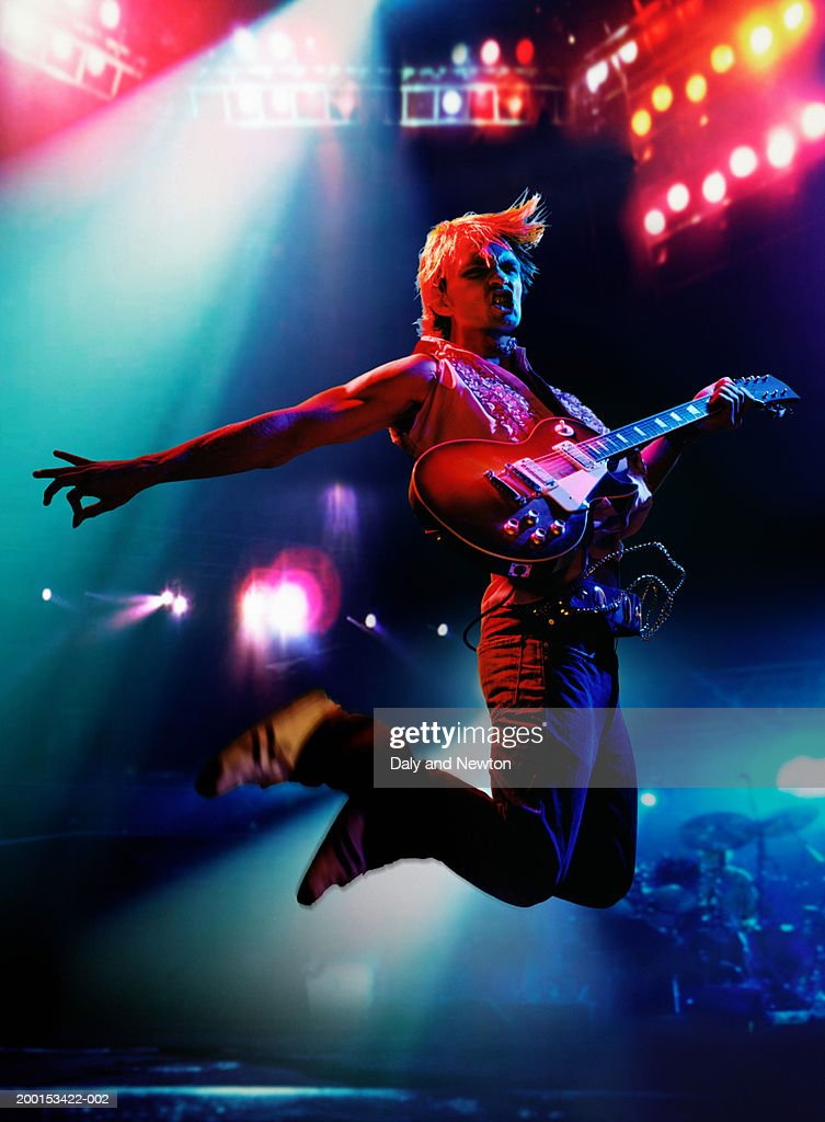 Man in air, holding electric guitar on stage