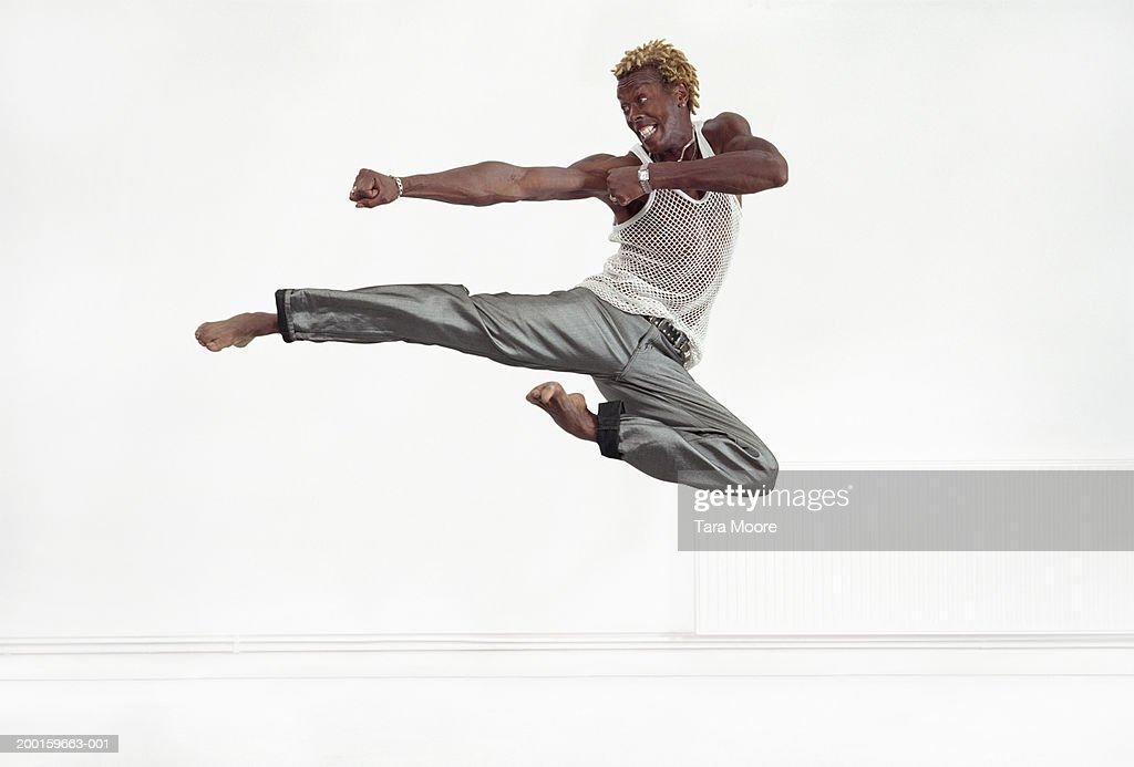Man in air performing martial arts kick : Stock Photo