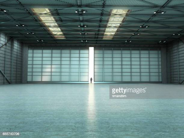 Man in an empty warehouse with door open
